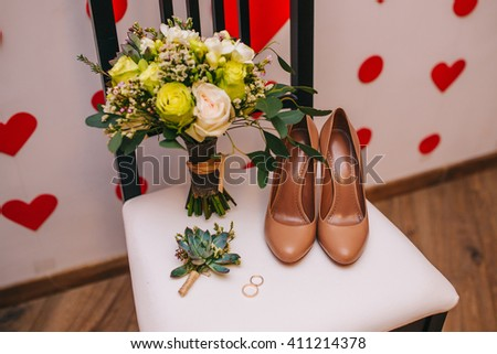 wedding bouquet and bridesmaid shoes, boutonniere white on white chair - stock photo
