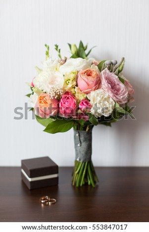 Wedding bouquet and delicate little brown box with wedding rings on a wooden surface