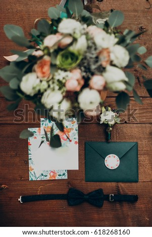 wedding bouquet and invitation. stylish modern flowers and floral invitation boutonniere and bow tie on wooden background top view. flat lay of rustic wedding  morning. space for text