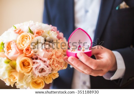 Wedding bouquet and rings on hand of groom - stock photo
