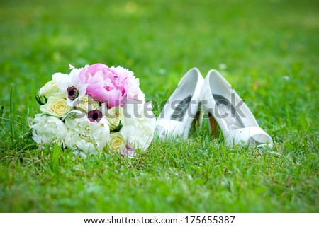 wedding bouquet and shoes lying down on green grass