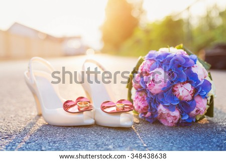 Wedding bouquet and shoes with rings laid on the ground - stock photo