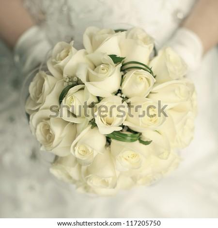 wedding bouquet at bride's hands. studio shot - stock photo