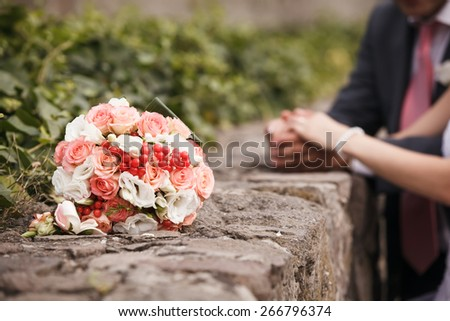Wedding bouquet close up. Bride's and groom's hands in background. Shallow depth of field - stock photo