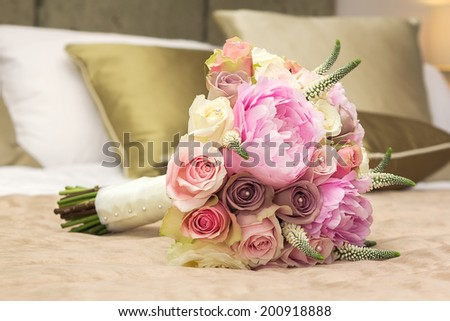 Wedding bouquet for bride on the bed - stock photo
