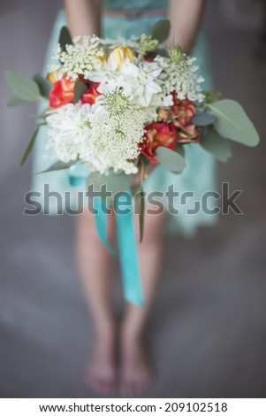 Wedding bouquet in a rustic style in the hands of the bride - stock photo