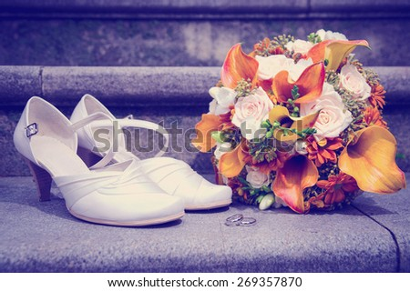 Wedding bouquet in autumn colors, white bride's shoes and rings on stairs with instagram effect retro vintage filter - stock photo