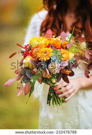 Wedding bouquet in bride's hands close-up - stock photo