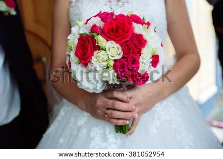 Wedding bouquet in brides hands - stock photo
