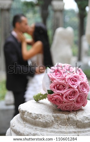 Wedding bouquet  in focus and couple in the background - stock photo