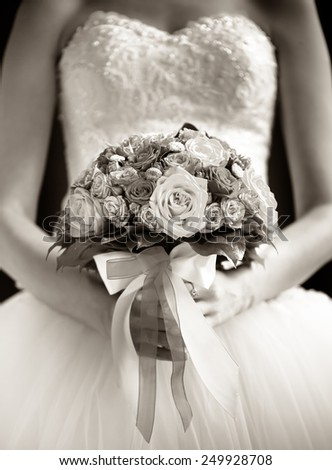 Wedding bouquet in hands of the bride. Black and white - stock photo