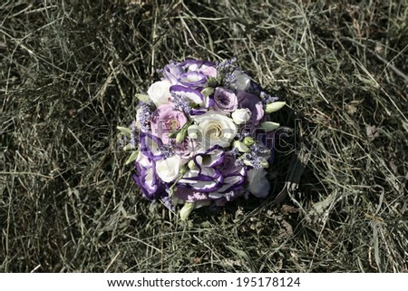 wedding bouquet in hay , Wedding bouquet of pink and white roses lying on grass , wedding bouquet in straw , hay - stock photo