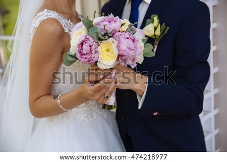 Wedding bouquet in marriage couple hands
