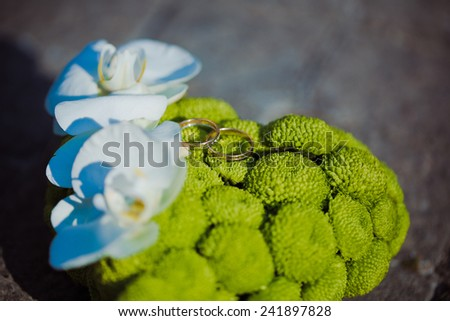 Wedding bouquet in the form of heart of roses and hydrangeas and wedding rings - stock photo