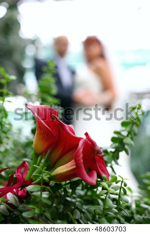 Wedding bouquet in the grass on the rear can see the newlyweds - stock photo