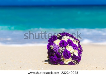 Wedding bouquet lying on the sand on a tropical beach. Blue sea in the background. - stock photo