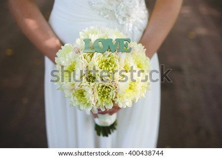 Wedding bouquet of asters in the hands of the bride - stock photo