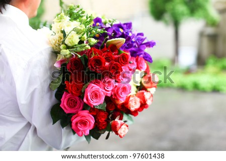 Wedding bouquet of beautiful colorful roses which are ready to present for bride and groom. - stock photo