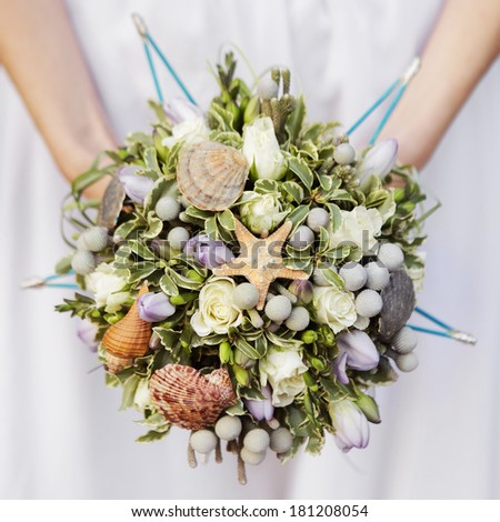 wedding bouquet of beige roses and leaves decorated with shells - stock photo