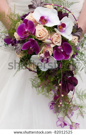 wedding bouquet of beige roses and purple orchids - stock photo