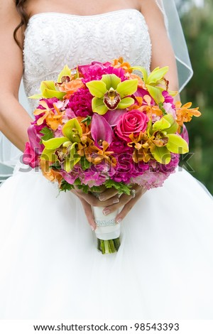Wedding bouquet of flowers held by a bride. Pink, Orange, and Green