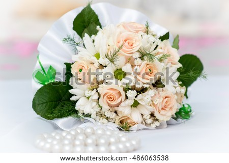 Wedding bouquet of flowers on a white background with beads ahead