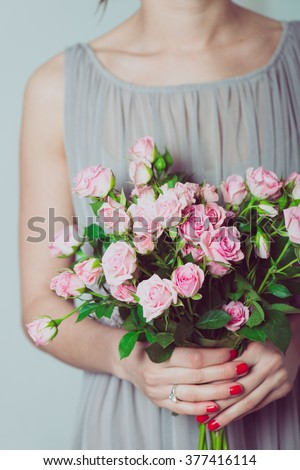 Wedding bouquet of flowers, young bridesmaid holding a bouquet of pink roses.  - stock photo