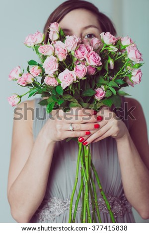 Wedding bouquet of flowers, young bridesmaid holding a bouquet of pink roses, and looking over the flowers - stock photo