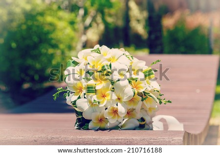 wedding bouquet of frangipani on the bench - stock photo