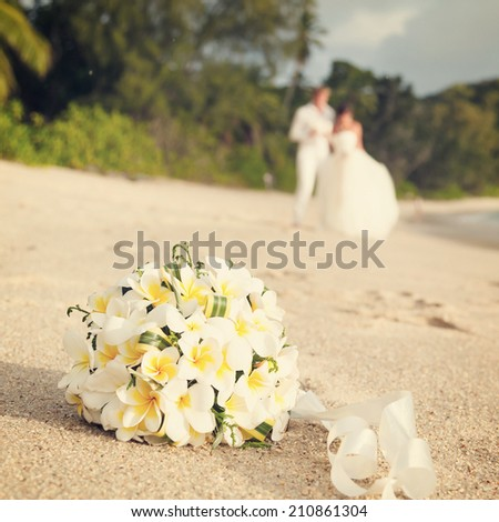wedding bouquet of jasmine or frangipani with newlyweds on the beach in the Seychelles - stock photo