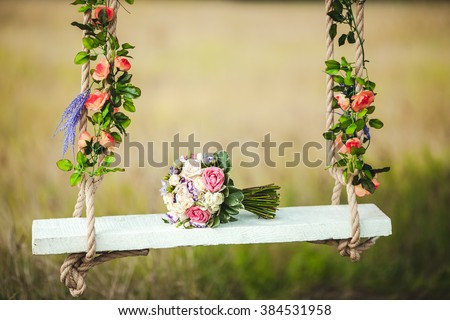 Wedding bouquet of peonies lying on a white bench swing decorated with fresh flowers. - stock photo