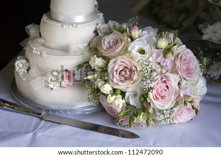 wedding bouquet of pink and white roses alongside the cake