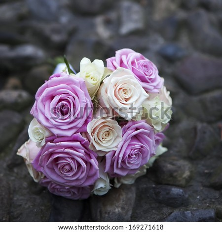 wedding bouquet of pink and white roses lying on roadway - stock photo