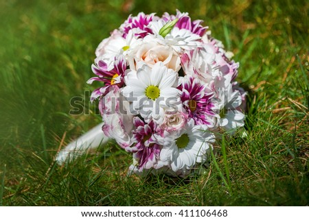Wedding bouquet of purple and white flowers lying on grass - stock photo