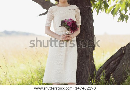 Wedding bouquet of red and pink roses and peonies, in the hands of the bride in the park - stock photo