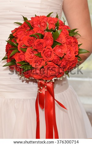 wedding bouquet of red roses in the hands of the bride - stock photo