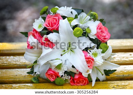 Wedding bouquet of roses and lilies for bride at a wedding party. - stock photo