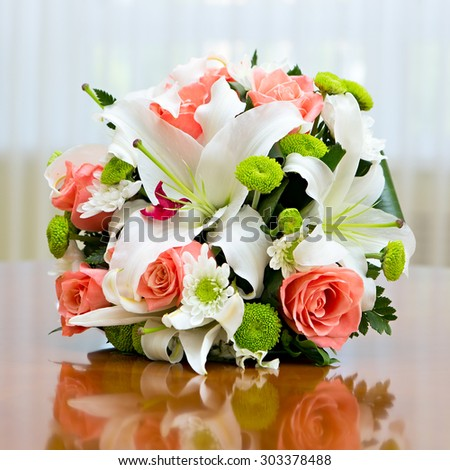 Wedding bouquet of roses and lilies for bride at a wedding party. Wedding bouquet of roses and lilies on the table against the background of a bright window.