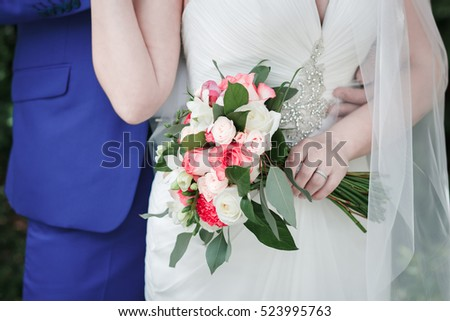 Wedding bouquet of roses, freesias and carnations in the hands of the bride