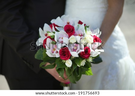 wedding bouquet of tender tones in the hands of the newlyweds