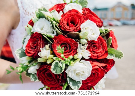 Wedding bouquet of the bride in hands. Flowers red and white roses