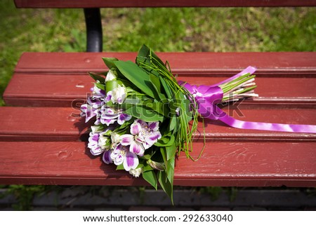 Wedding bouquet of various flowers on a wooden bench - stock photo