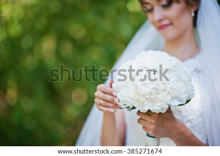 Wedding bouquet of white carnation at hand of bride
