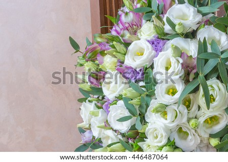 Wedding bouquet of white flowers eustoma, purple alstroemeria and green eucalyptus leaves on a beige background.