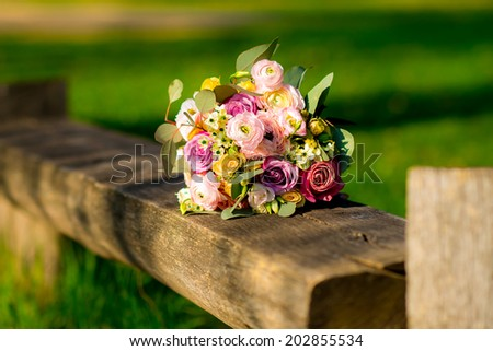 Wedding bouquet of yellow and white red pink roses and blue fresia lying on wood on the park - stock photo
