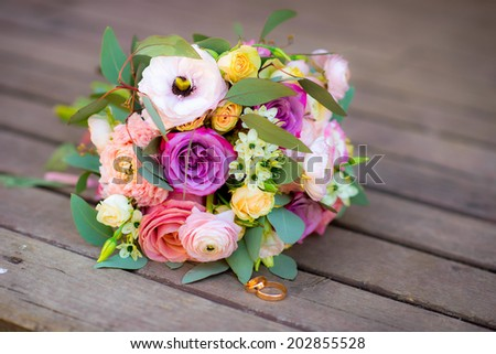 Wedding bouquet of yellow and white red pink roses and blue fresia lying on wooden floor - stock photo