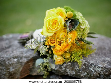 Wedding bouquet of yellow roses on stone wall outside - stock photo