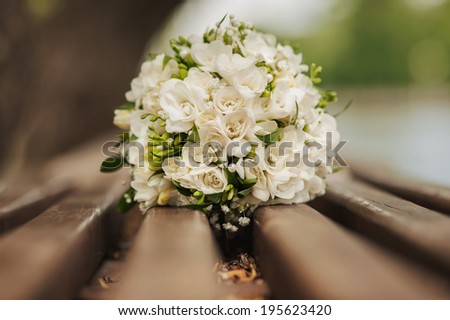 Wedding bouquet on a bench - stock photo