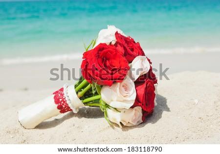Wedding bouquet on the beach - stock photo