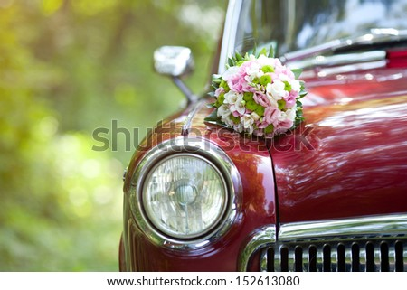 Wedding bouquet on vintage wedding car - stock photo
